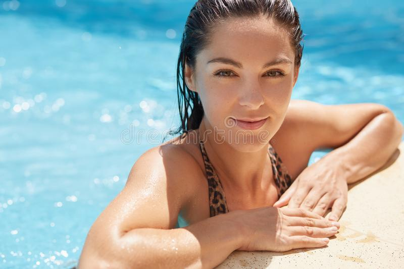 Nahes hohes Porträt der magnetischen zarten jungen Frau, die nass Haar nachdem dem Schwimmen in Swimmingpool, betrachtend direkt  stockfotografie
