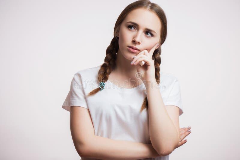 Nahes hohes Porträt der schönen jungen Frau, die aufwärts denkt und schaut stockfotografie