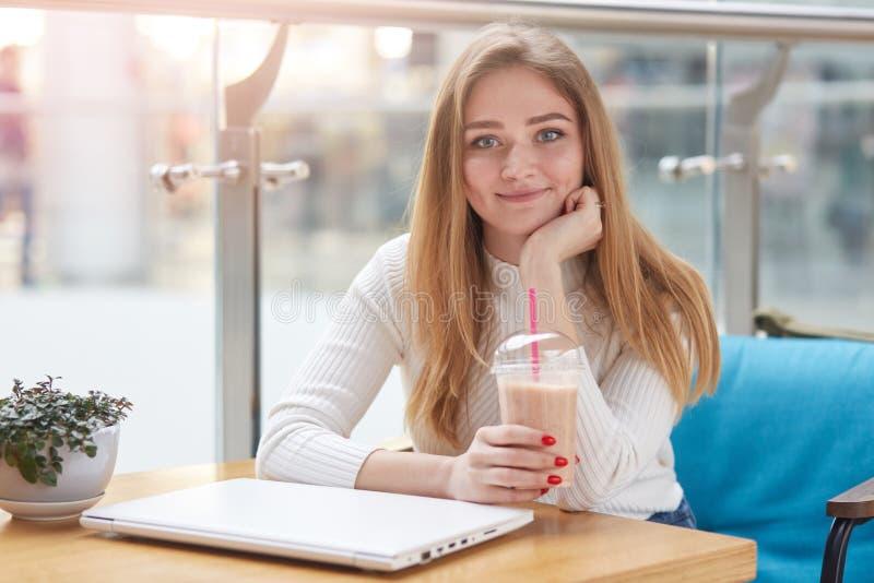 Nahes hohes Porträt der schönen jungen kaukasischen Frau mit dem langen blonden Haar, das im Café, Trinkmilchcocktail, Rest haben lizenzfreie stockbilder
