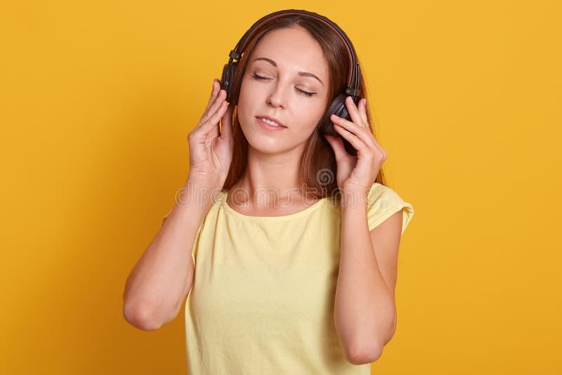Nahes hohes Porträt der schönen kaukasischen Frau, die Musik über Kopfhörer, entspannend beim Haben der Freizeit hört und werfen  stockbild