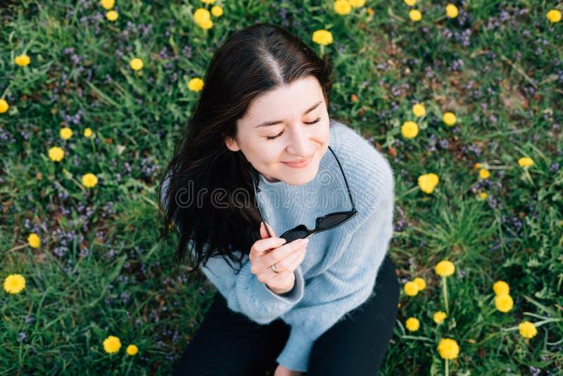 Nahes hohes Porträt der schönen tausendjährigen jungen Frau in der Sonnenbrille, die auf Wiese mit Blumen und Gras der gelben Kam stockfotografie