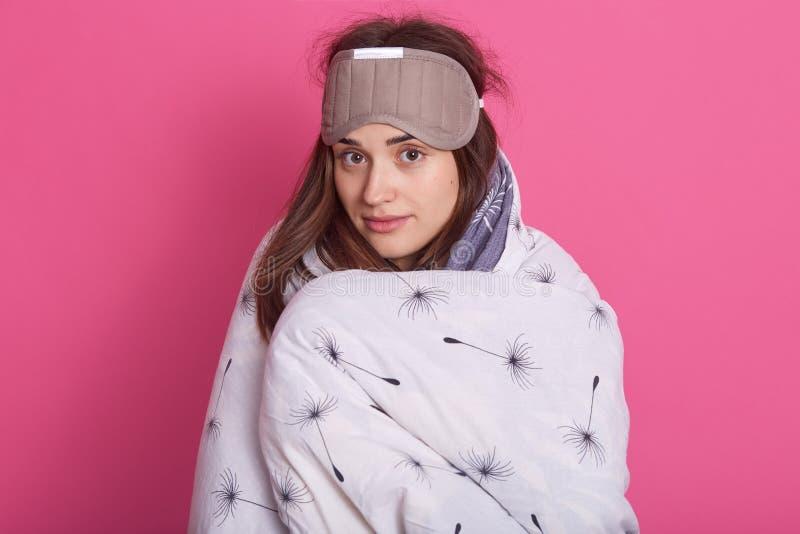 Nahes hohes Porträt der schläfrigen Frau mit Schlafenmaske auf Kopf und tragender Decke über rosafarbenem Studiohintergrund, scha stockfotografie