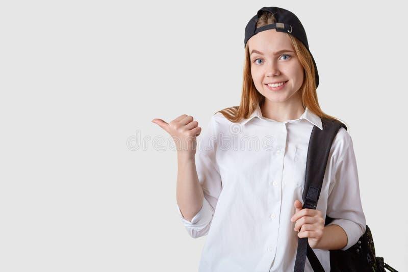 Nahes hohes Porträt der tragenden Kappe der attraktiven Studentin, der weißen Bluse und des Rucksacks, beiseite zeigend mit ihrem stockfoto