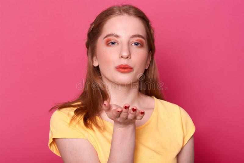 Nahes hohes Porträt des attraktiven reizend reizenden Mädchens mit perfekter Frisur und ausgezeichnete bilden und senden Luftkuß, stockfoto