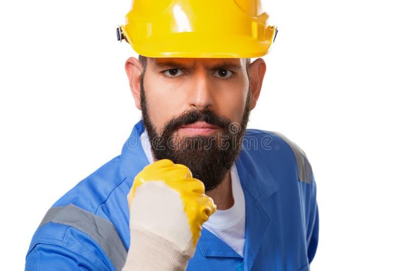 Nahes hohes Porträt des bärtigen verärgerten Mannerbauers im gelben Sturzhelm und blauen in der Uniform, die mit der Faust üb stockfoto