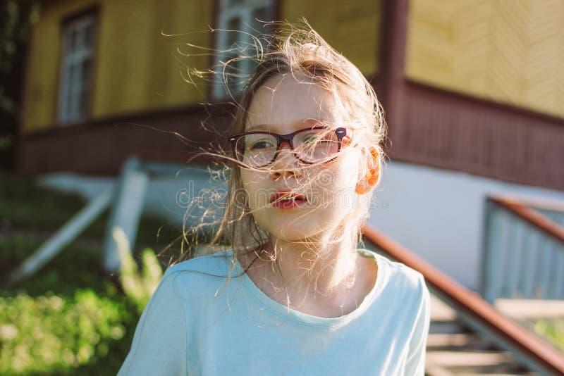 Nahes hohes Porträt des bezaubernden Mädchens in den Gläsern auf dem alten Holzhaushäuschen des Hintergrundes, Sommerzeit in der  lizenzfreie stockfotografie