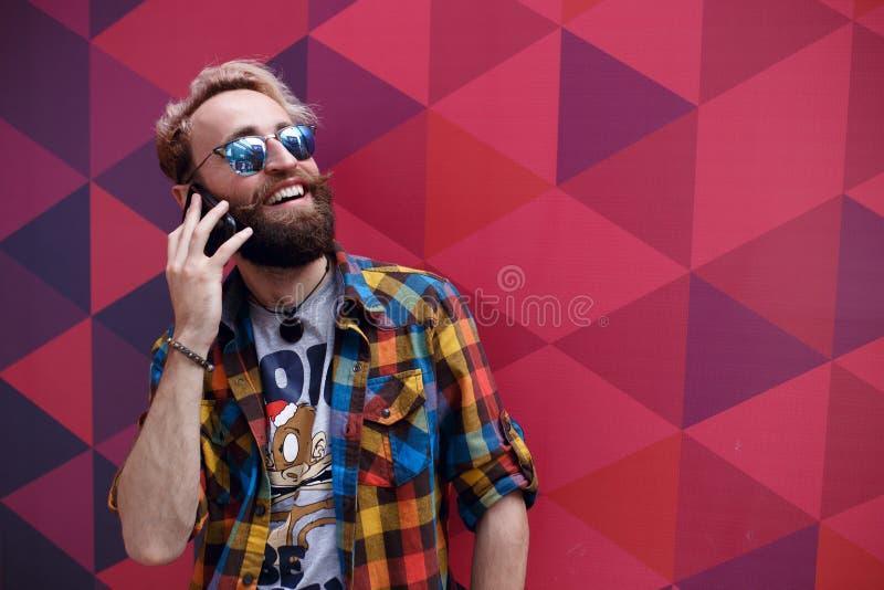 Nahes hohes Porträt des glücklichen reifen Kerls, der am Handy spricht und, lokalisiert auf einem bunten Hintergrund lächelt stockfotos