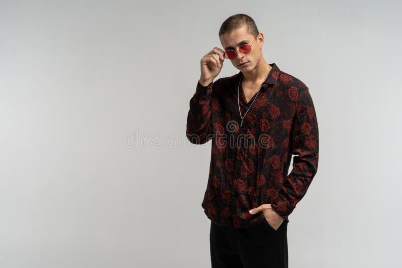Nahes hohes Porträt des hübschen stilvollen Mannes in der runden Sonnenbrille lizenzfreie stockbilder