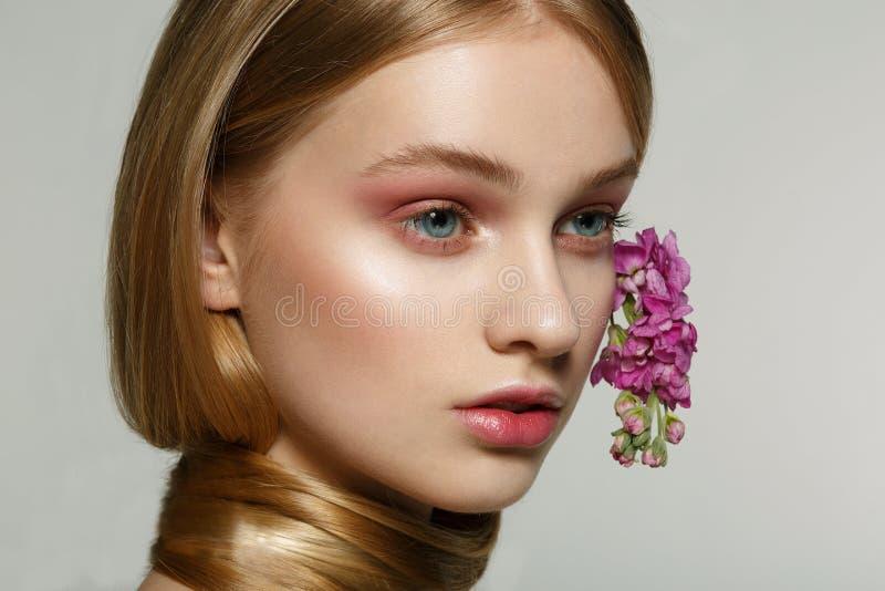 Nahes hohes Porträt des jungen Mädchens mit blauen Augen, helles Make-up, Hals eingewickelt im Haar, purpurrote Blumen gekräuselt stockfotos