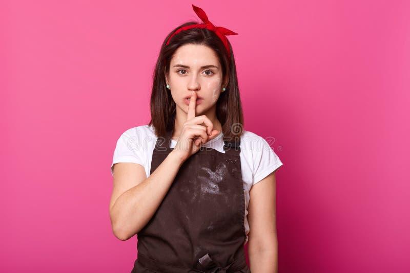 Nahes hohes Porträt des jungen reizend Mädchens mit dem Finger auf ihren Lippen, macht die Ruhegeste, weiblich trägt roten Hairba lizenzfreie stockfotos