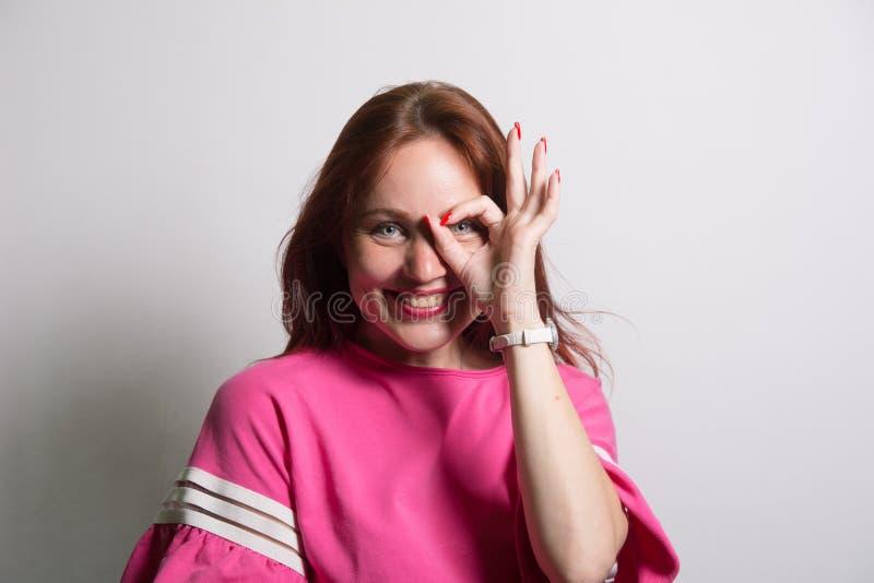 Nahes hohes Porträt des kaukasischen weiblichen Lächelns der schönen frohen Rothaarigen, die weißen Zähne demonstrierend und durc lizenzfreie stockfotografie