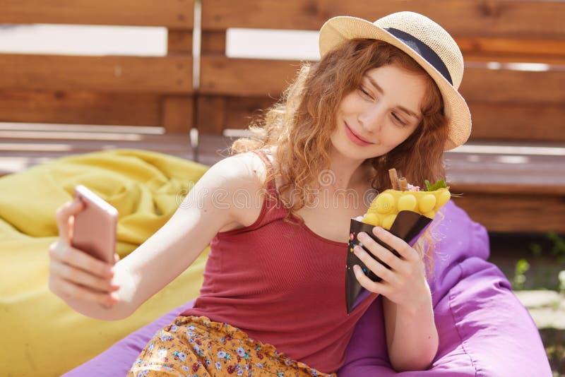 Nahes hohes Porträt des lächelnden entspannten jungen Mädchens, das selfie, Smartphone in einer Hand halten nimmt und essen die N lizenzfreie stockfotos