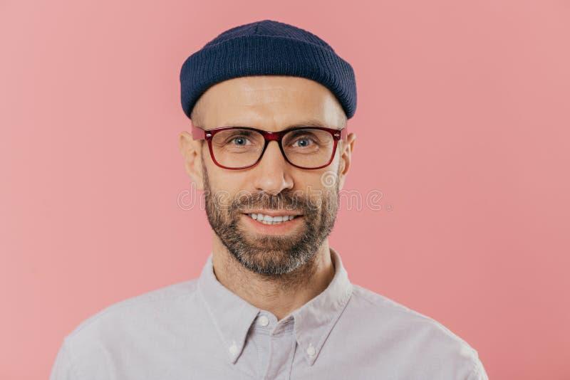 Nahes hohes Porträt des lächelnden unrasierten Mannes, freut sich gute Nachrichten, trägt den Hut und Hemd, Blicke mit den Augen, stockfotos
