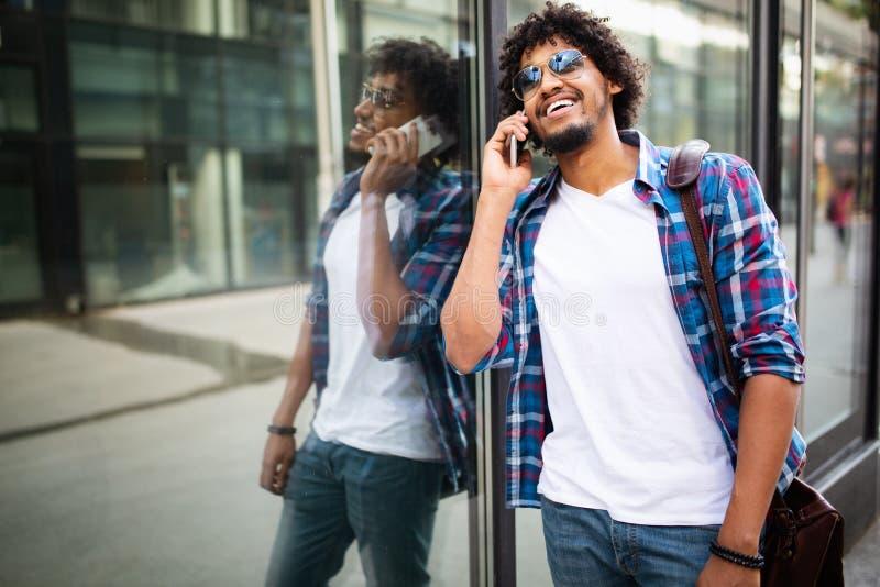 Nahes hohes Porträt des Lachens des schwarzen jungen Mannes, der am Handy spricht und weg schaut stockbilder