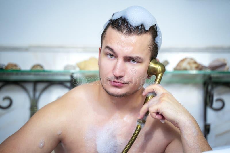 Nahes hohes Porträt des lustigen Mannes, der den Spaß sich entspannt in der Dusche nimmt Bad mit dem Schaum, herum täuschend hat  lizenzfreies stockbild