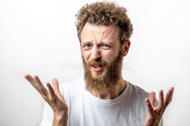 Nahes hohes Porträt des mürrischen jungen bärtigen Mannes im T-Shirt, das Kamera betrachtet lizenzfreies stockbild