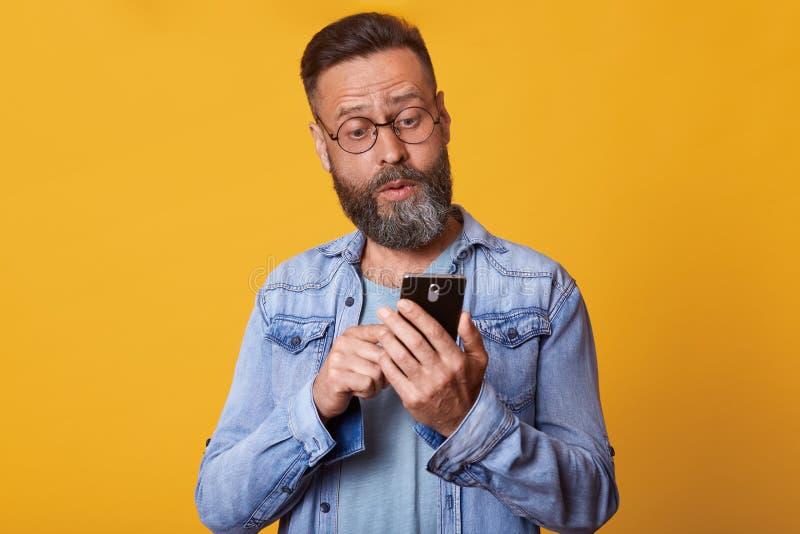 Nahes hohes Porträt des mittleren gealterten kaukasischen Mannes unter Verwendung des smarphone mit entsetztem und überraschtem G lizenzfreie stockfotografie
