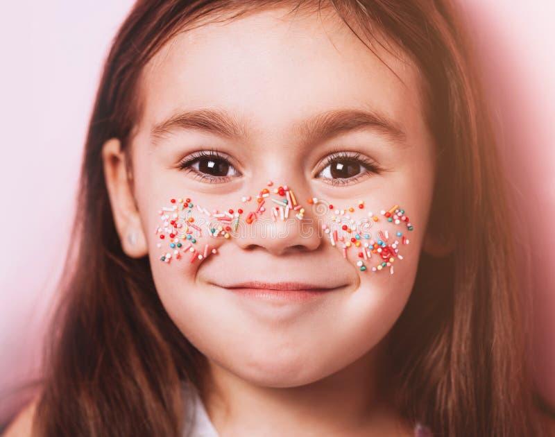 Nahes hohes Porträt des netten kleinen Mädchens mit buntem Belag auf Gesicht auf rosa Hintergrund stockbild