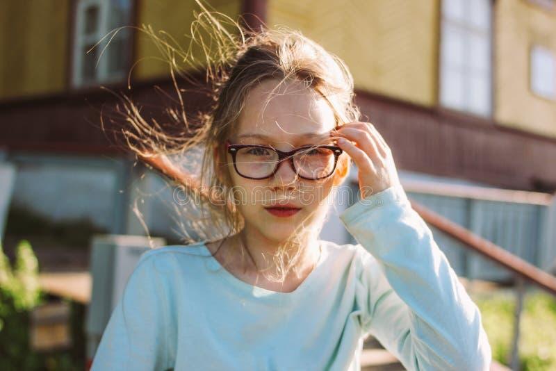 Nahes hohes Porträt des reizend lächelnden Mädchens in den Gläsern auf altem Holzhaushäuschen des Hintergrundes, Sommerzeit in de stockfotos