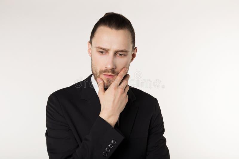 Nahes hohes Porträt des schönen bärtigen Geschäftsmannes mit der stilvollen Frisur, die schwarzen Anzug trägt stockfotografie
