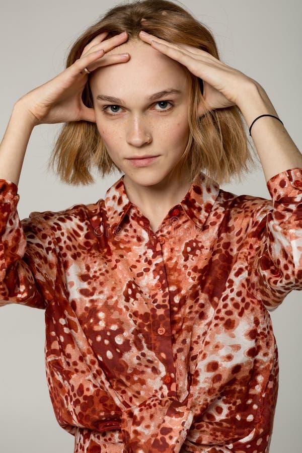 Nahes hohes Porträt des schönen blonden Mädchens im roten Hemd mit Durchdringen in der Nase stockbilder