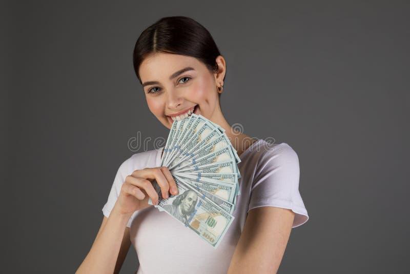 Nahes hohes Porträt des schönen netten brunette Mädchenvertretungsbündels Dollars lizenzfreie stockbilder