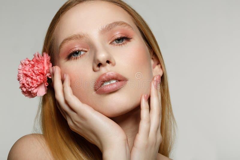 Nahes hohes Porträt des träumerischen blonden Mädchens mit dem modischen Make-up, das ihr Gesicht berührt stockfoto