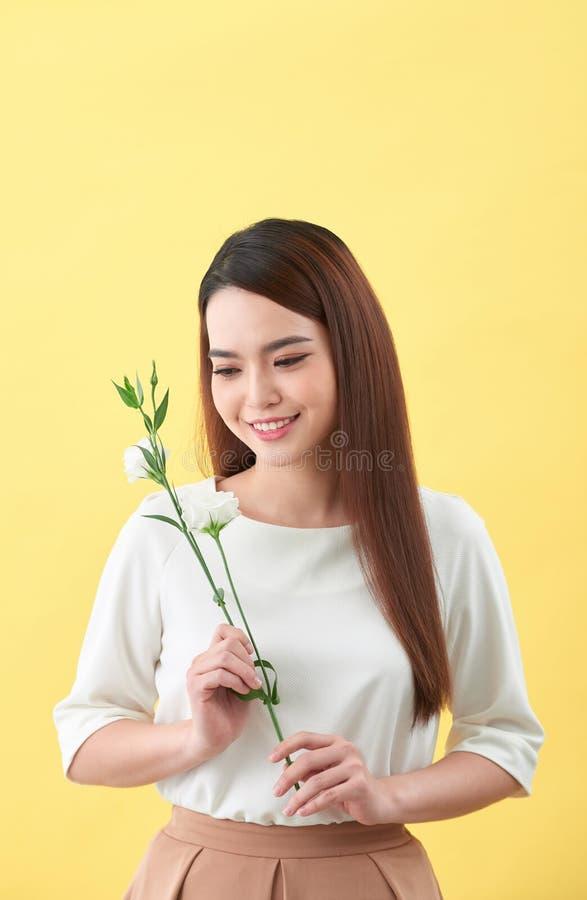 Nahes hohes Porträt einer attraktiven Holdingblume der jungen Frau lizenzfreie stockbilder