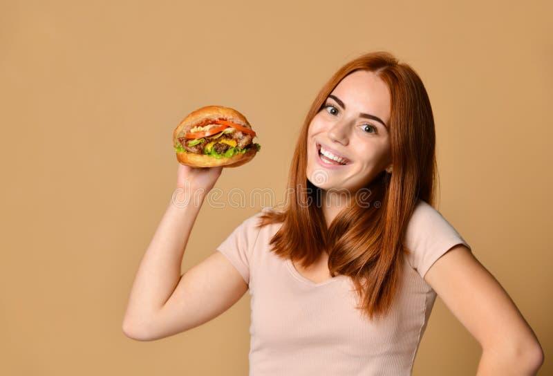 Nahes hohes Porträt einer hungrigen jungen Frau, die Burger über nacktem Hintergrund isst stockfoto