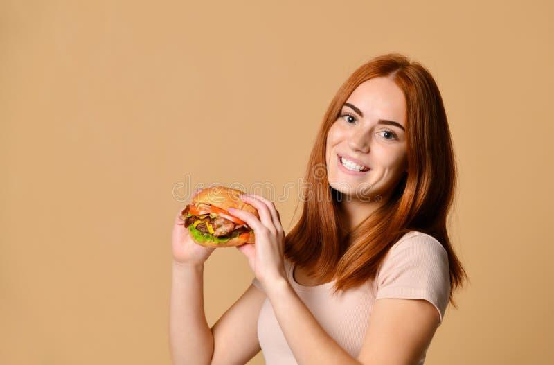 Nahes hohes Porträt einer hungrigen jungen Frau, die Burger über nacktem Hintergrund isst stockbild