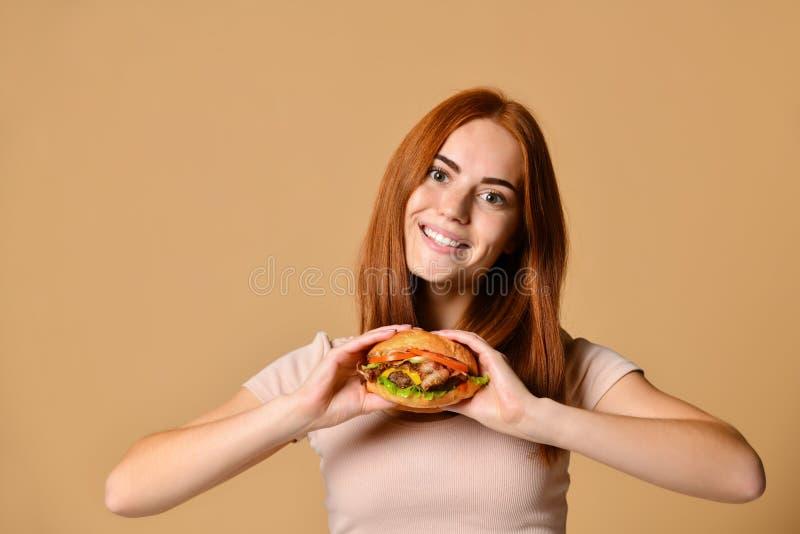 Nahes hohes Porträt einer hungrigen jungen Frau, die den Burger lokalisiert über nacktem Hintergrund isst stockbild