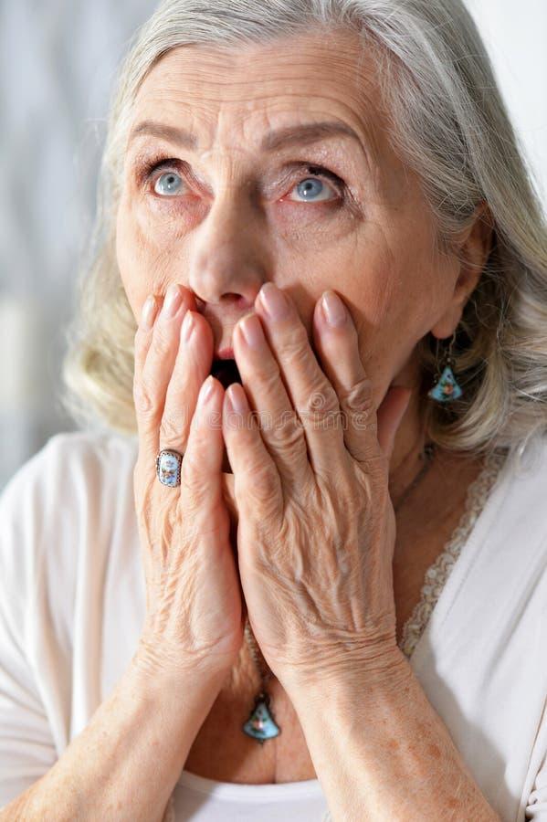Nahes hohes Porträt einer traurigen älteren Frau stockfotografie