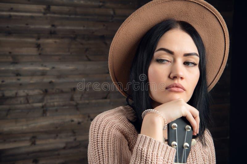 Nahes hohes Porträt eines attraktive brunette Frau tragenden sweather und Hut mit schöner Gitarre Hölzerner Hintergrund stockfoto