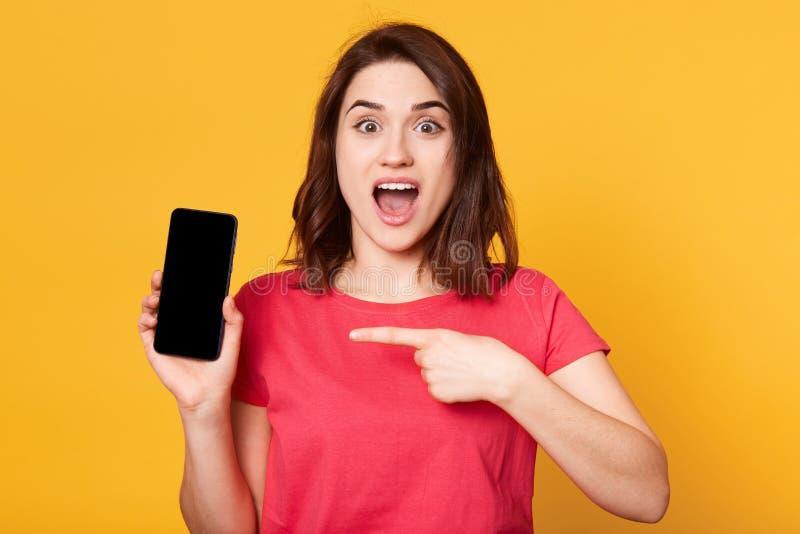 Nahes hohes Portr?t von ?berraschten europ?ischen brunette Punkten der jungen Frau mit ihrem Vorderfinger am leeren Bildschirm, h stockfoto
