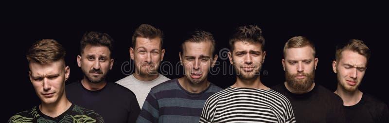 Nahes hohes Porträt von den jungen Männern lokalisiert auf schwarzem Studiohintergrund lizenzfreies stockfoto