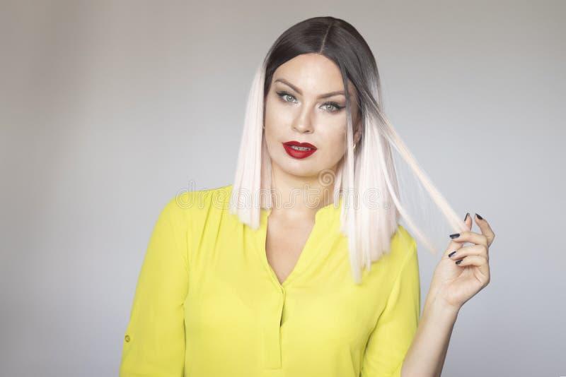 Nahes hohes Porträt von jungen schönen Blondinen über grauem Hintergrund lizenzfreies stockfoto