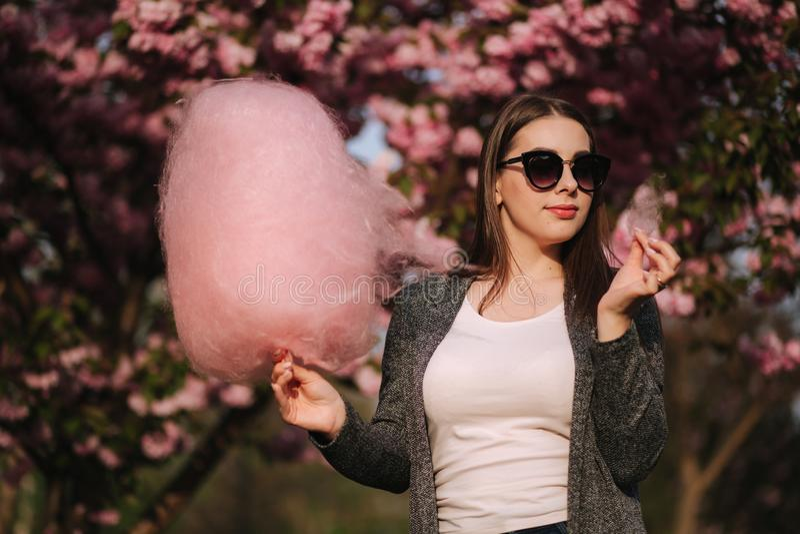 Nahes hohes Portr?t des attraktiven jungen M?dchens, das Zuckerwatte vor rosa Kirschbl?te-Baum isst stockfoto