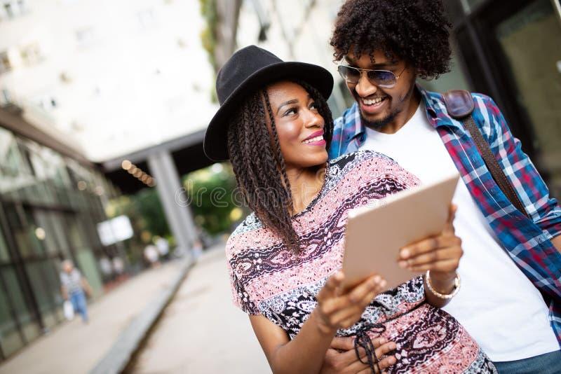 Nahes hohes Portr?t von gl?cklichen jungen schwarzen Paaren unter Verwendung einer digitalen Tablette zusammen stockbilder