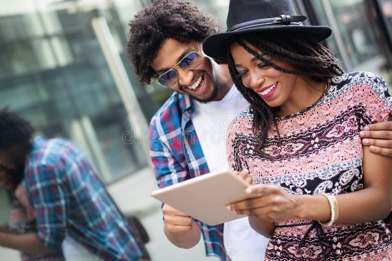 Nahes hohes Portr?t von gl?cklichen jungen schwarzen Paaren unter Verwendung einer digitalen Tablette zusammen stockfoto