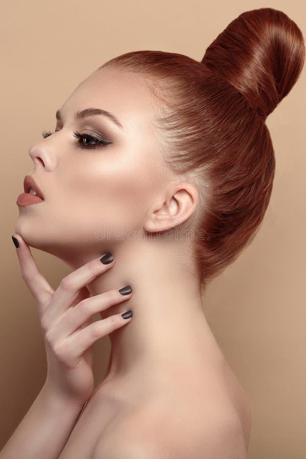Nahes hohes Profilporträt des schönen rothaarigen Modells mit ihrem Haar rieb zurück in ein hohes Brötchen stockbild