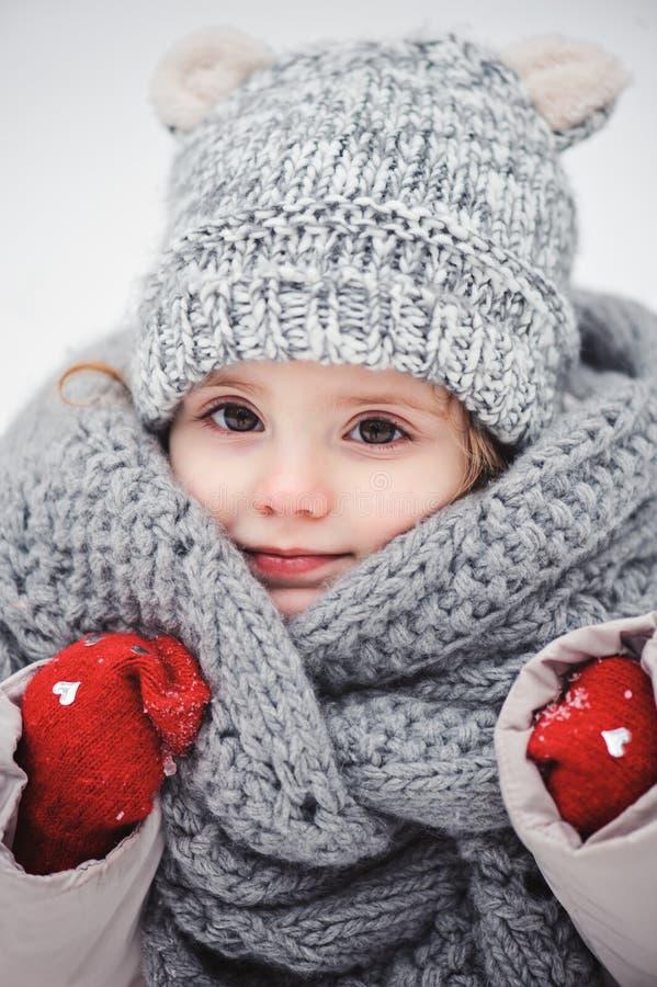Nahes hohes vertikales Porträt des Winters des entzückenden lächelnden Babys in der grauen Strickmütze und im Schal stockfotografie