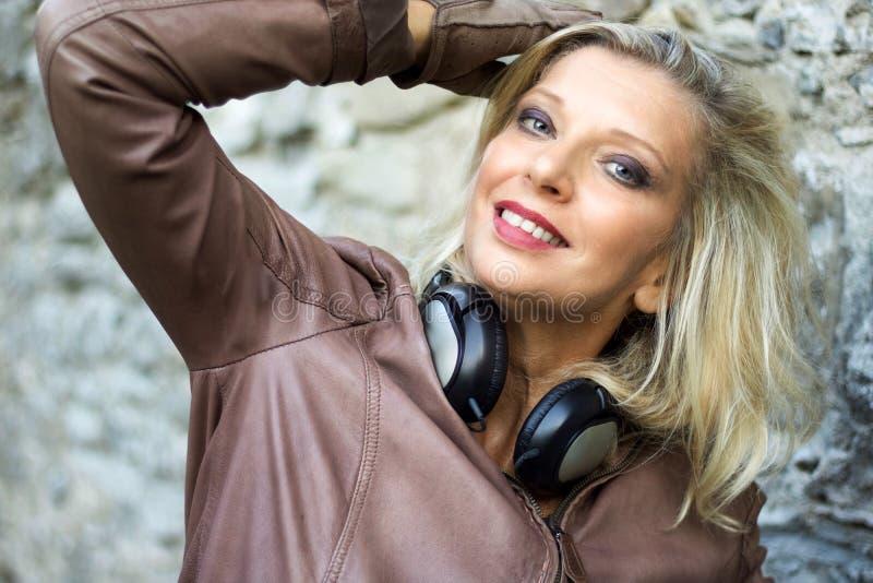 Nahes Porträt der blonden Frau mit dem Kopfhörerlächeln stockfoto