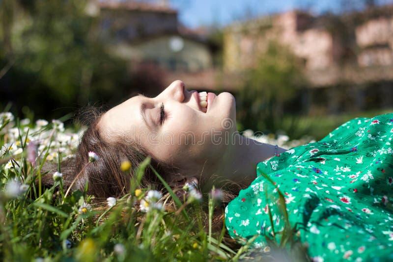 Nahes Porträt der jungen Frau mit der reinen Haut, die sich auf einem Gebiet hinlegt lizenzfreies stockbild