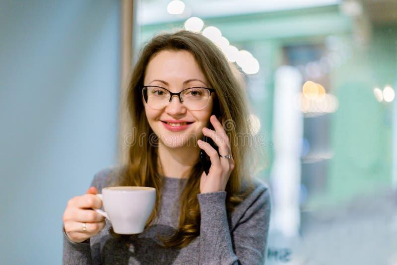 Nahes Porträt einer hübschen jungen lächelnden Frau, die im Café mit einer Tasse Tee oder Kaffee sitzt, Fenster auf dem Fenster stockbild