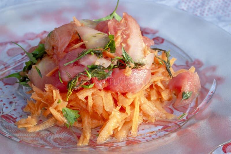 Nahes Trieb der Karotte und Tomate mischen Öl fallengelassenen Salat auf transparenter Platte stockfotos