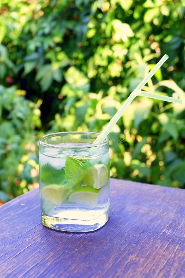 Nahrhaftes Detoxwasser mit Kalk und Minze in einem Glas auf dem hölzernen Hintergrund stockbilder