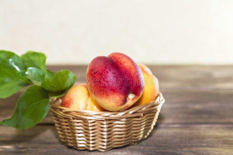 Nahrung, Ernte, frische Frucht Reife Frucht des saftigen Pfirsiches mit Wassertropfen und der Blätter eines Weidenkorbes auf eine lizenzfreie stockfotografie