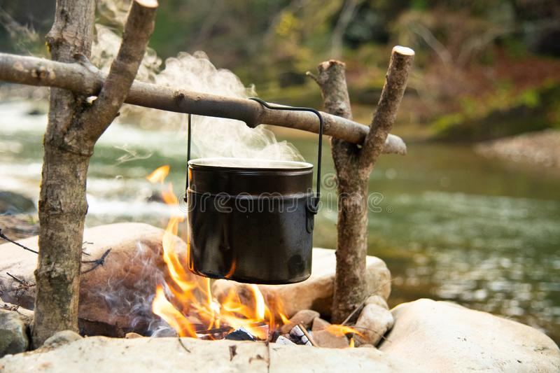 Nahrung im Topf über dem Lagerfeuer kochen im Freien lizenzfreie stockfotos