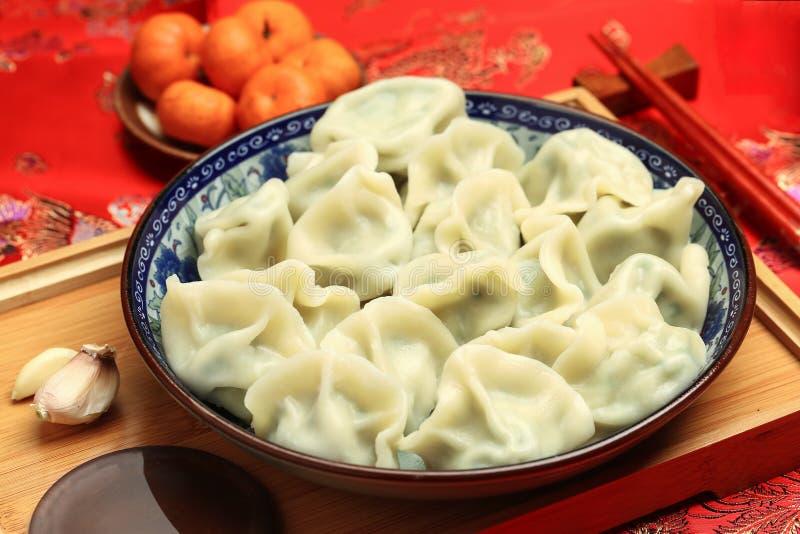 Nahrung neuen Jahres Chinese Jiaozi, Frühlingsfestmehlklöße auf rotem Hintergrund des traditionellen Frühlingsfests lizenzfreies stockfoto
