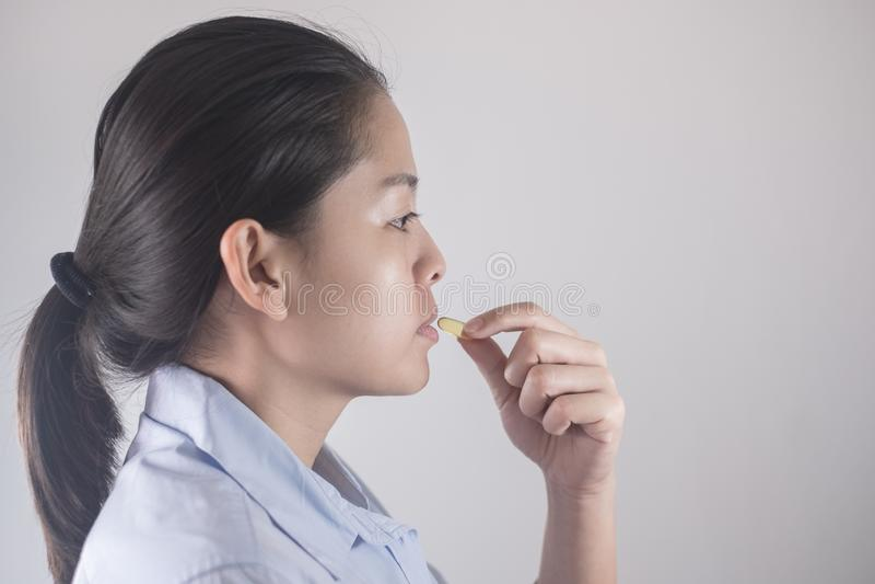 Nahrungs-Konzepte der gesunden Ernährung und der Diät Vitamin und Ergänzung schöne asiatische junge Frau, die gelbe Fischölpille  stockbilder